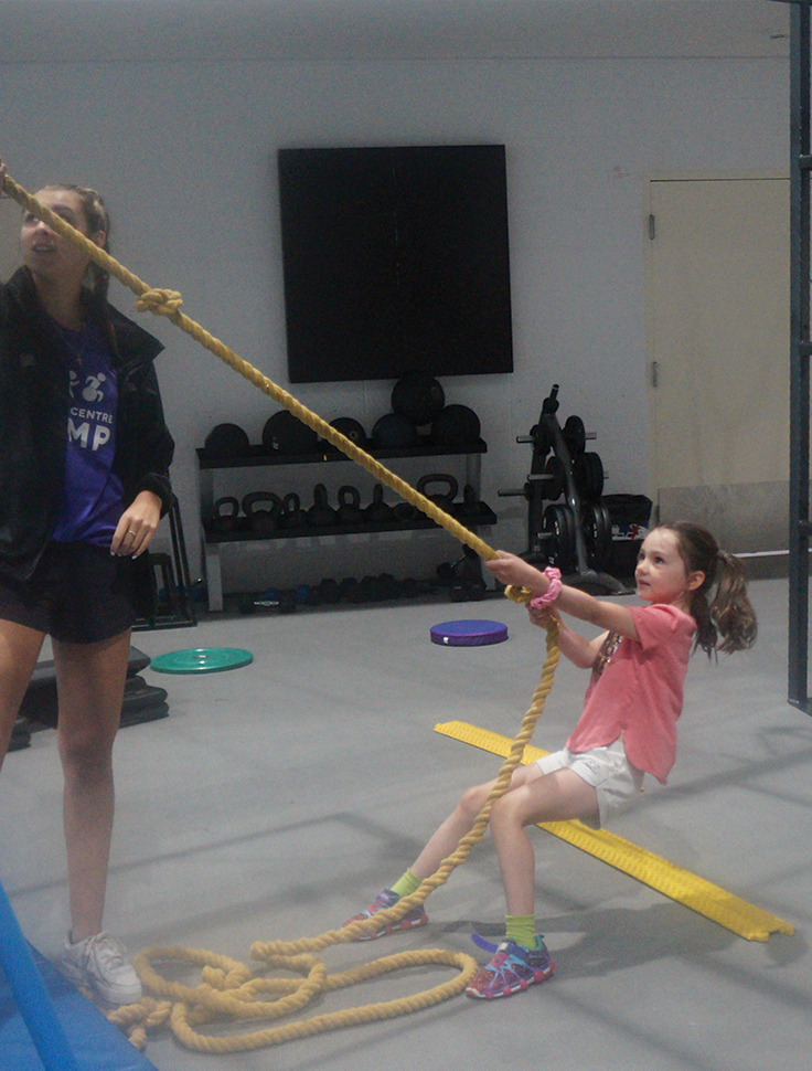 A young girl pulling a rope at an organized registered program