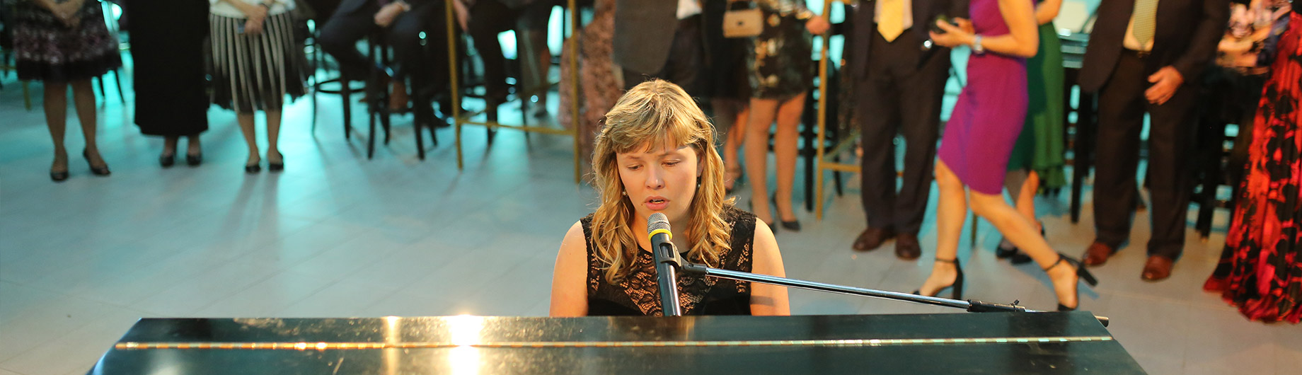 A female live musician and vocalist performing at an Abilities Centre event