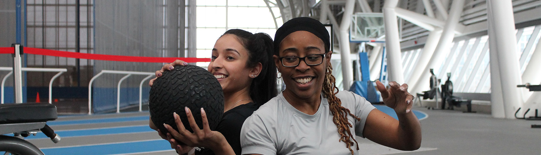 Two female members working out together with medicine ball
