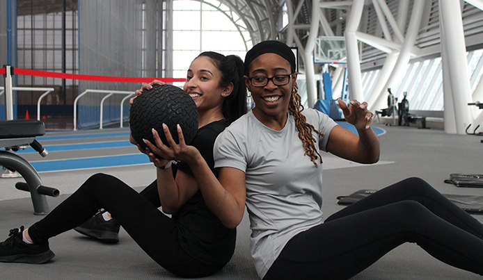 Two female members in the Fieldhouse stretching with a medicine ball
