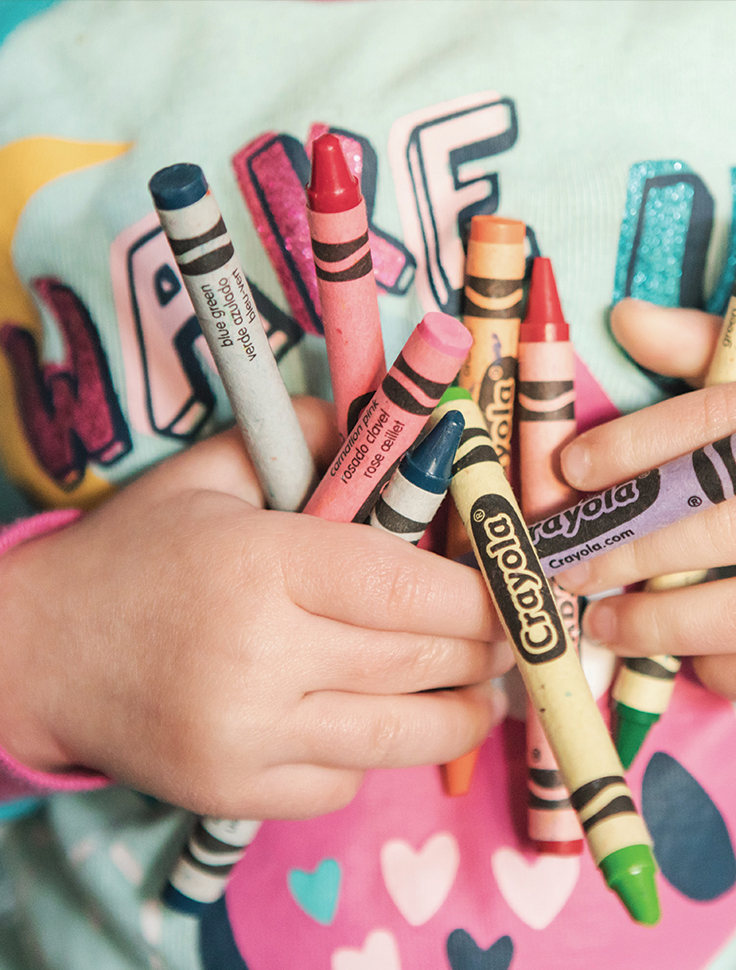 a child holding a handful of crayons