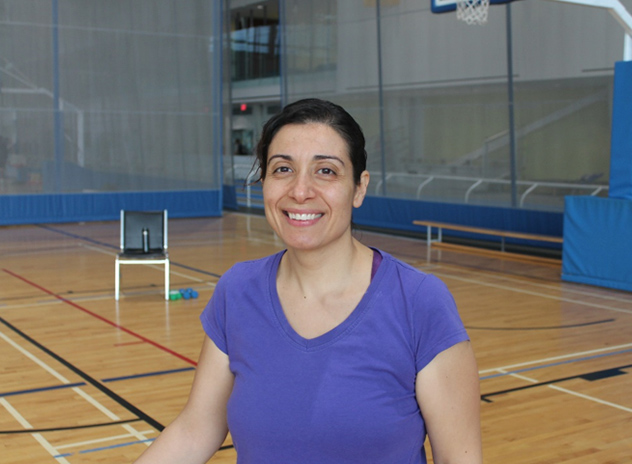 Member Christine in the Fieldhouse smiling at the camera