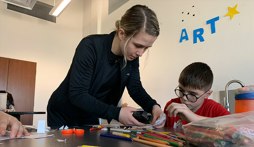 Abilities Centre program coordinator instructing and assisting youth participant with art and craft program