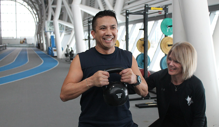 A trainer assisting a member with a kettle bell