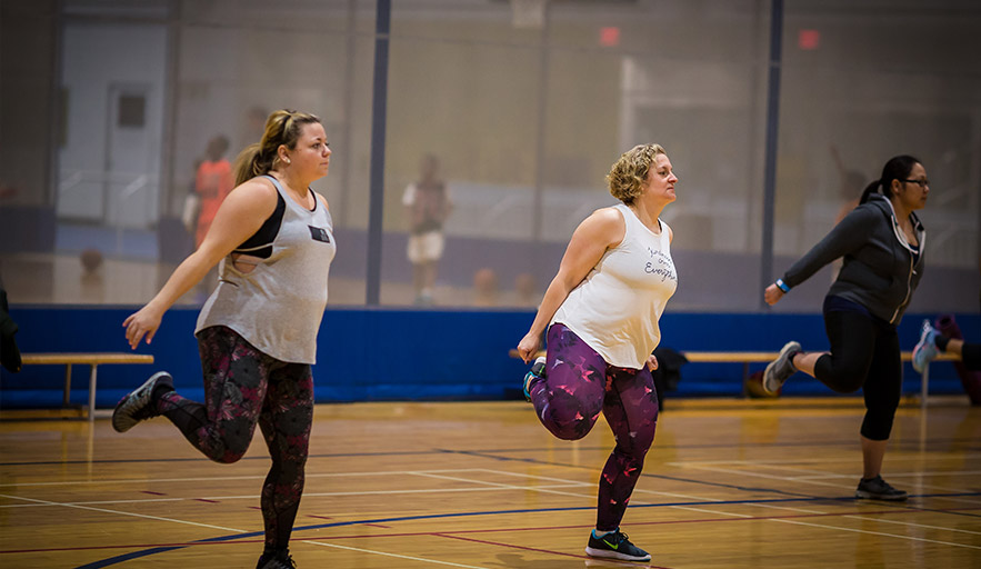 Three women actively engaged in a class workout on court