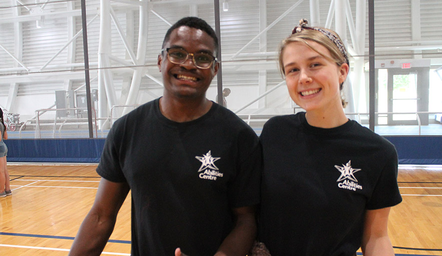 Two Abilities Centre staff coordinators actively smiling in fieldhouse