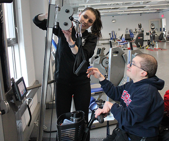 Abilities centre trainer instructing member with equipment