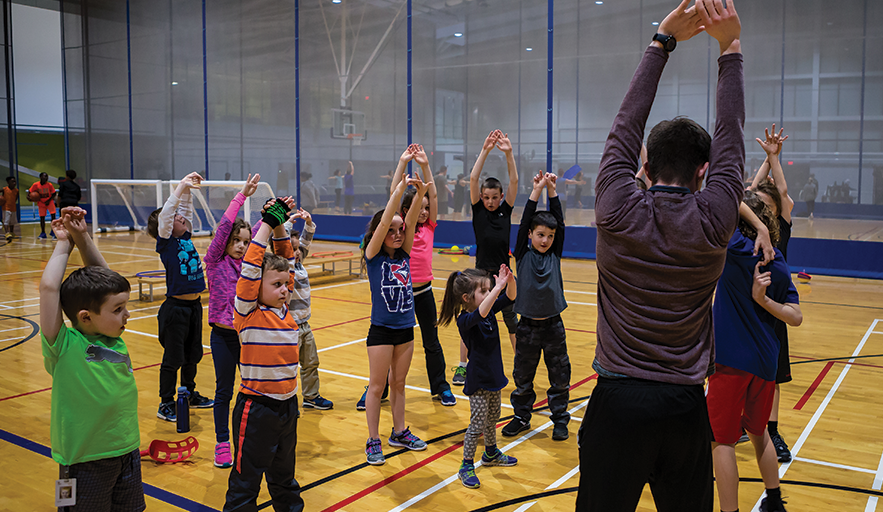 Abilities Centre Sport and Recreation coordinator leads young boys and girls through stretching exercise