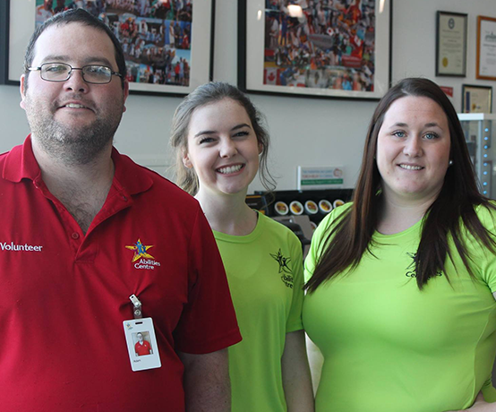 Two female volunteers and 1 male volunteer smile in Atrium at Abilities Centre