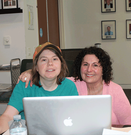 Two participants of the program smile behind a laptop sitting at a table