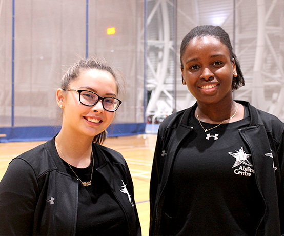 Two female staff in Abilities Centre Fieldhouse smiling in preparation for program work
